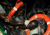 African would-be immigrants try to climb aboard a Spanish civil guard vessel after their makeshift boat capsized during a rescue  operation at sea off the coast of Fuerteventura November 12, 2004. Their boat, carrying some 36 immigrants, overturned as the civil guards' vessel manouevered to rescue them off Fuerteventura, the closest of Spain's Canary Islands to the African coast. Some 29 were rescued and seven disappeared. - RTXN19U